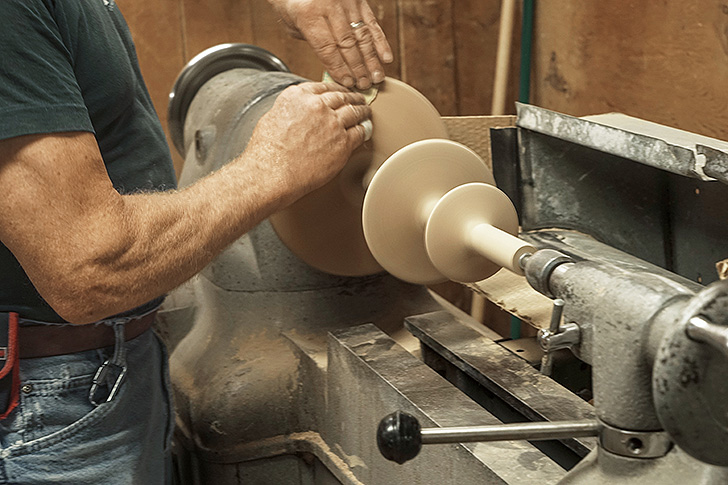 woodworker turning a table base
