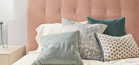 Millennial pink upholstered bed with pillows
