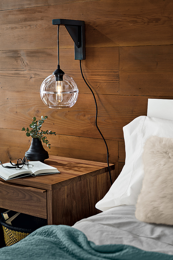 pendant light above a nightstand with a wall mount