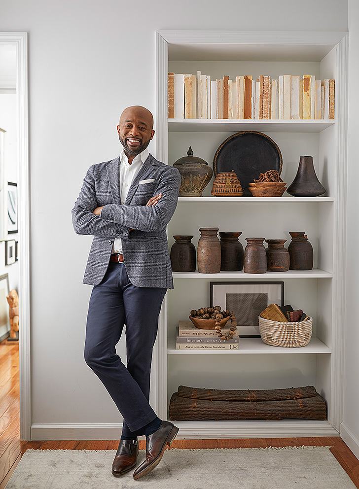 Designer Mikel Welch stands against a bookcase