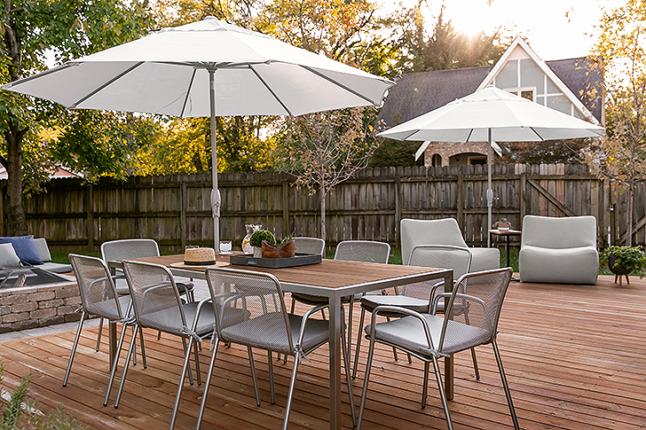 Dining chairs around an outdoor dining table with an umbrella